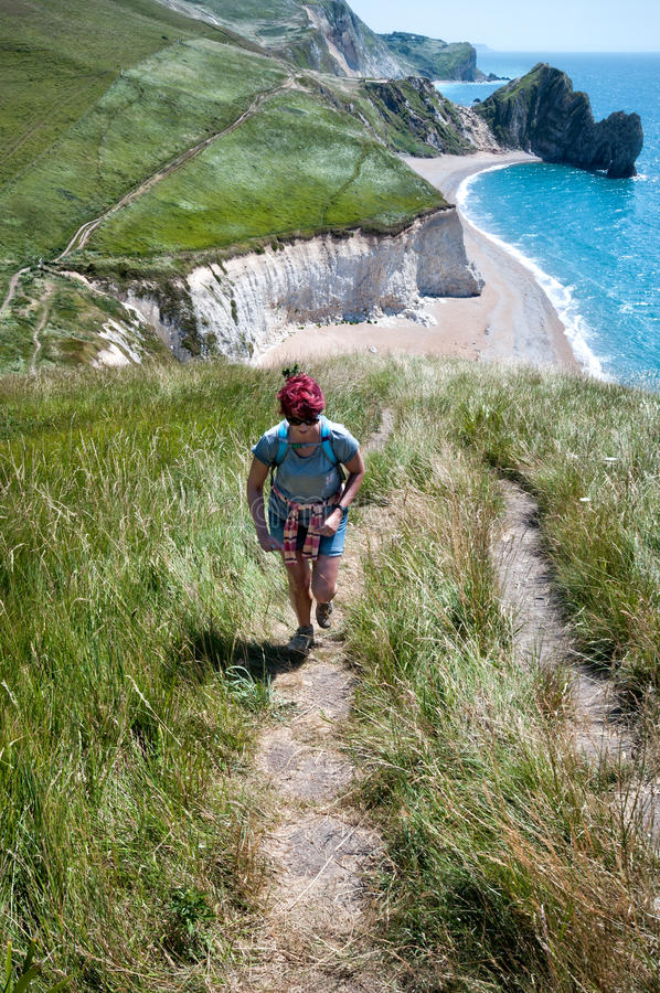 Female Hiker on coastal path. Attractive young woman hikes the South West Coastal Path, Dorset with Durdle Door in the distance. Part of The Jurassic coastline royalty free stock images