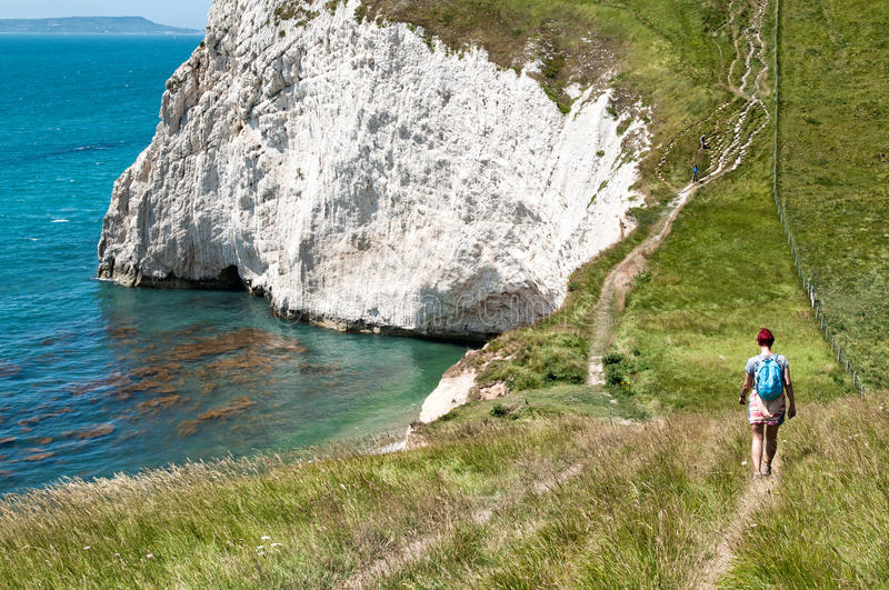 Female Hiker on coastal path. Attractive young woman hikes the South West Coastal Path, Dorset. Part of The Jurassic coastline of England, UK stock photos