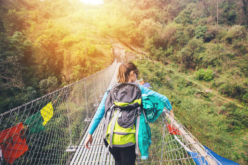 Female hiker crossing suspension footbridge in Himalayas. Female hiker crossing suspension footbridge and touching prayer flags stock image