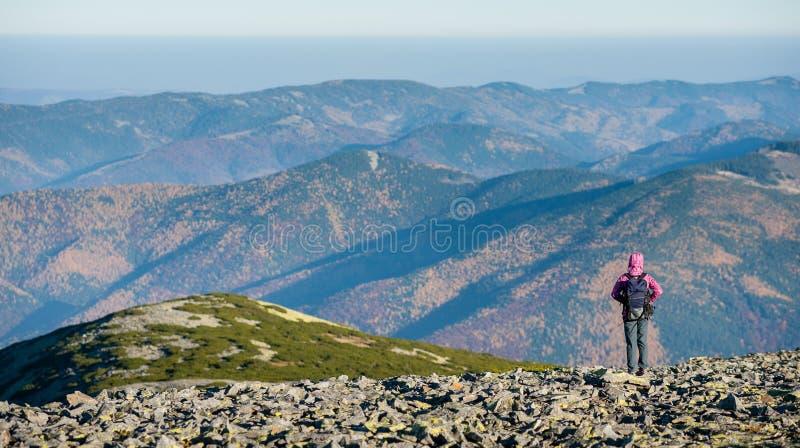 Female hiker enjoying beautiful overlook on the mountains. Female hiker standing on mountain plato enjoying beautiful overlook on the mountains with backpack on royalty free stock image
