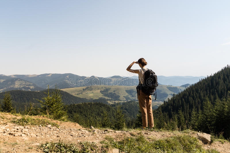 Young backpacker tourist girl stands top of the mountain and looks at hills with forests and meadows. stock photos