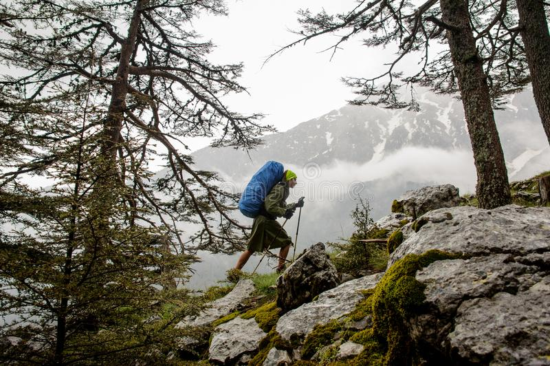 Female hiker goes up to top of the mountain. Female hiker in khaki raincoat with blue backpack goes up to top of the mountain royalty free stock images