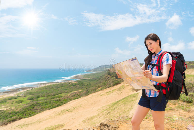 Female hiker holding map studying hiking route royalty free stock images