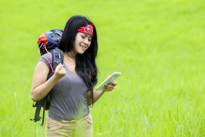 Female hiker looking at her smartphone royalty free stock image