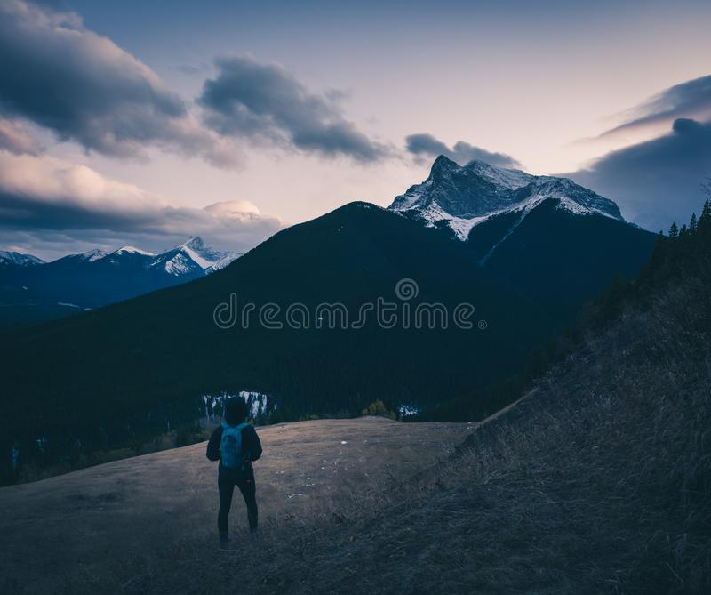 Female hiker looking out at the clouds near sunset stock photo