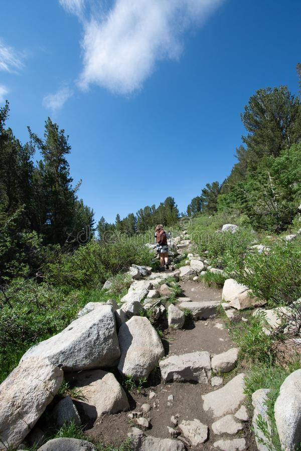 Female hiker makes her way on an uphill climb in the Little Lakes Valley hiking area of California Eastern Sierra Nevada mountains.  stock image