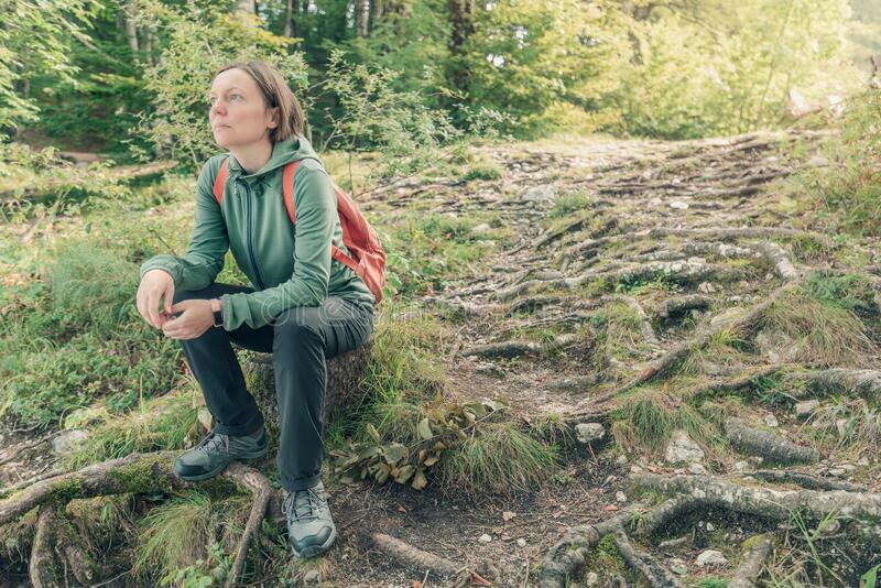 Female hiker resting and contemplating in forest royalty free stock photo