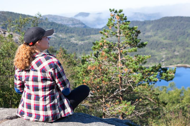 Female hiker resting on the edge of rocky cliff overlooking the Norwegian nature. Mountains lake. Norway stock photography