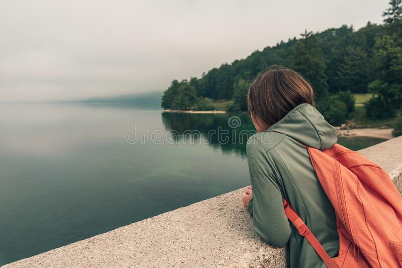 Female hiker standing on bridge and looking over lake stock photo