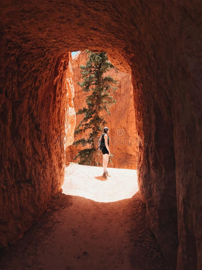 Female hiker standing in front of a Bryce Canyon Tunnel entrance during daytime stock images
