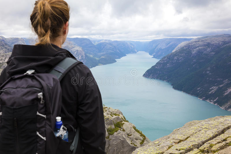 Female hiker standing at a high mountain in fjord. Dramatic clouds and female tourists hiking at a high mountain in a fjord. Preikestolen also known by the royalty free stock photo
