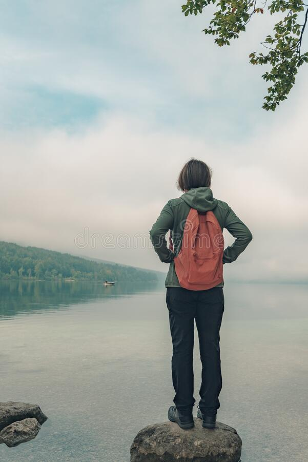 Female hiker standing on the rock and looking at lake stock image