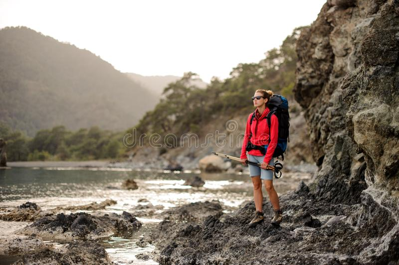 Female hiker stands with hiking sticks in hands stock photos