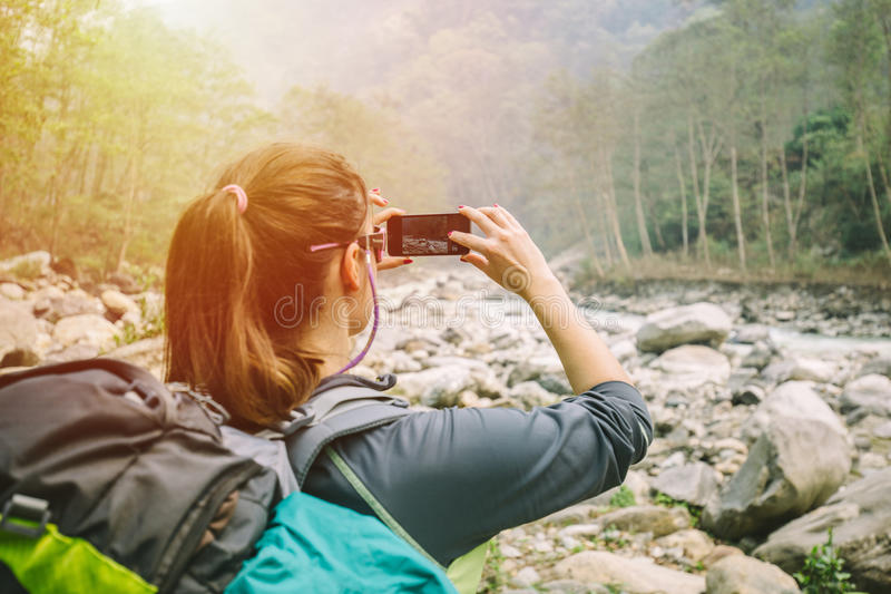 Female hiker taking photo of mountain river. Female hiker taking photo of Himalayan river Modi Khola, in region of Annapurna stock images