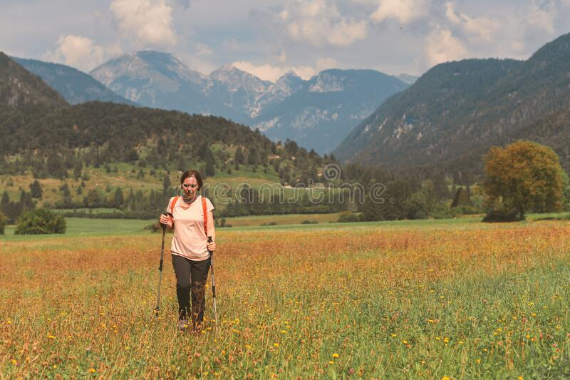 Female hiker is trekking in alpine countryside landscape in autumn stock photography