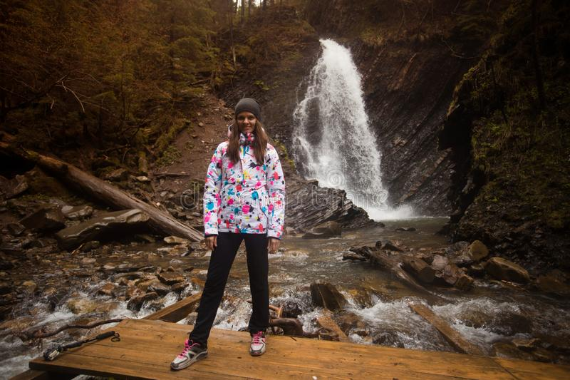 Female hiker walk near big mountains waterfall. stock photo