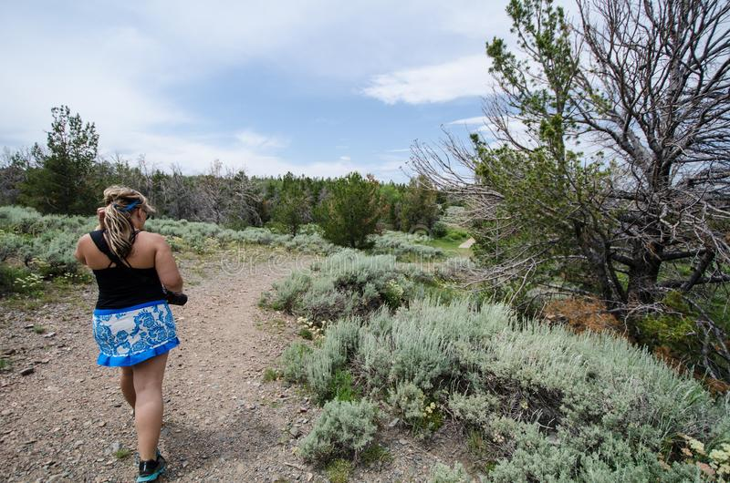 Female hiker walks on a dirt hiking trail in Miners Delight Wyoming to explore a ghost town royalty free stock images