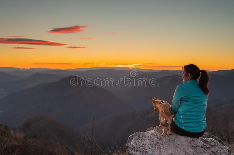 Female hiker watching the sunset sky with her dog on top of the hill royalty free stock image