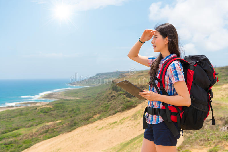 Female hiking backpacker using mobile computer. Young female hiking backpacker using mobile computer research route guidebook and making looking gesture enjoying royalty free stock image