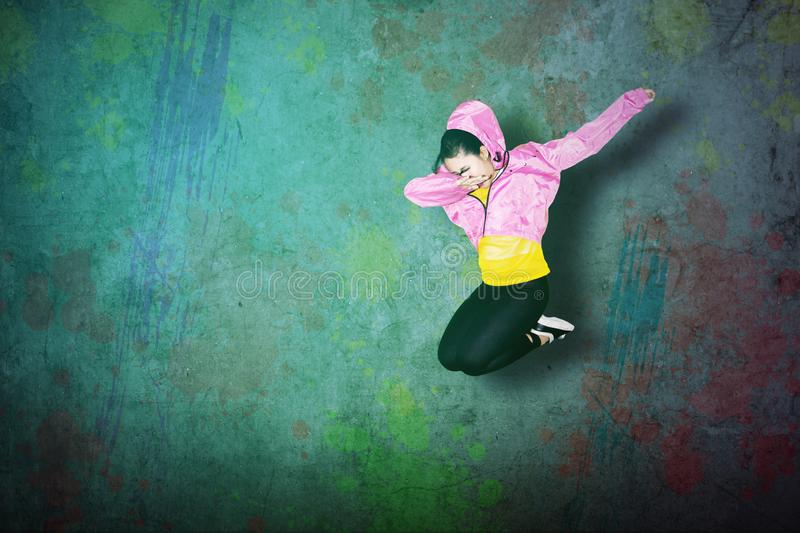 Female hip-hop dancer making dab dance. Female hip-hop dancer jumping while making dab dance with colorful concrete background stock photography
