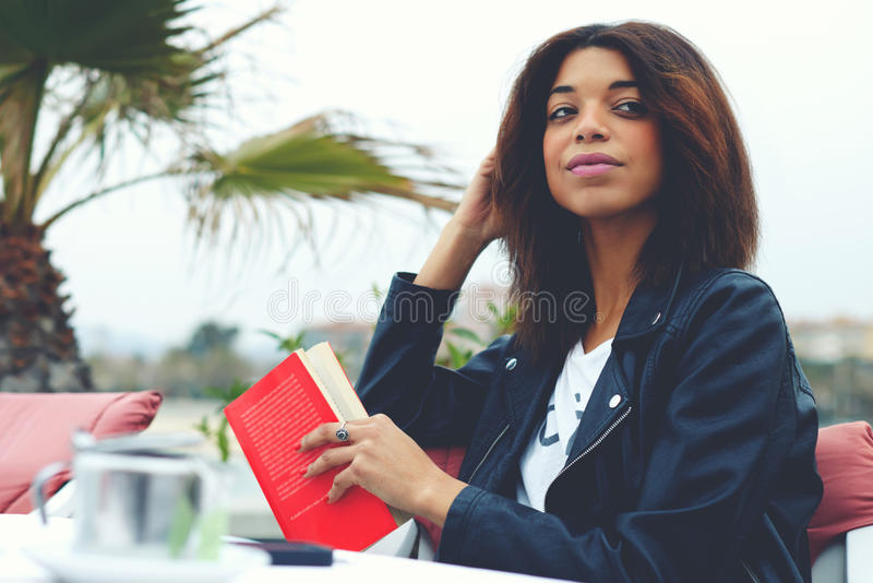 Female hipster enjoying her recreation time at weekend. Portrait of charming afro american woman sitting at the coffee shop terrace with book or novel looking stock photography