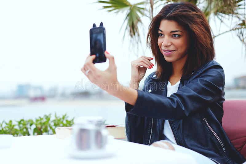 Female hipster taking a picture of herself on smartphone royalty free stock photo