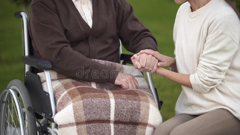 Female holding aged male hand, visiting granddad in hospital, nursing home stock photo