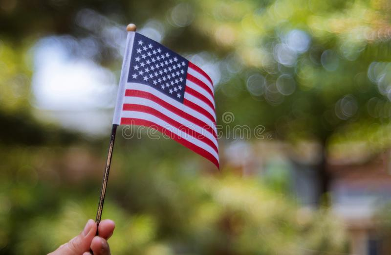 Female holding american flag outdoors on beautiful summer day. Independence Day stock image