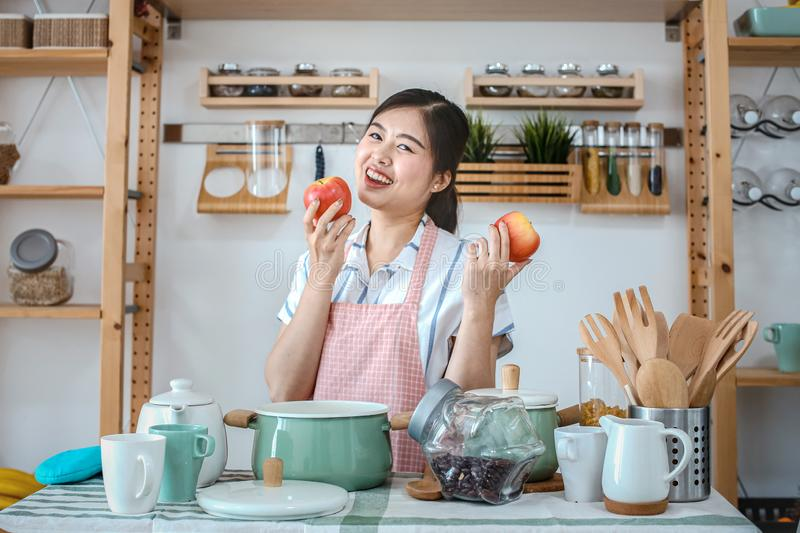 Female holding an apple in the kitchen. Portrait of a pretty woman holding apple healthy food in the kitchen. Happy woman which. Standing in cooking place stock image