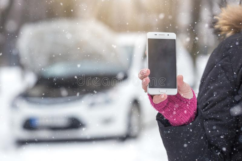 Female holding blank screen smartphone next to car with opened hood. Winter season road assistance concept. stock photo