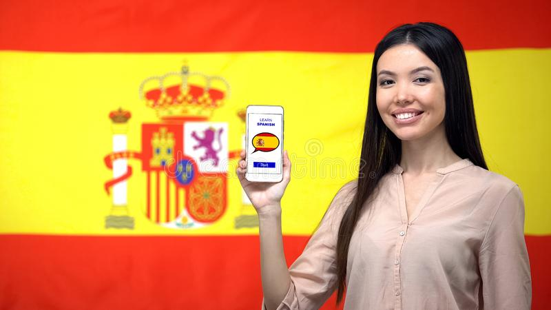 Female holding cellphone with learn Spanish app, flag on background, education. Stock photo royalty free stock photo