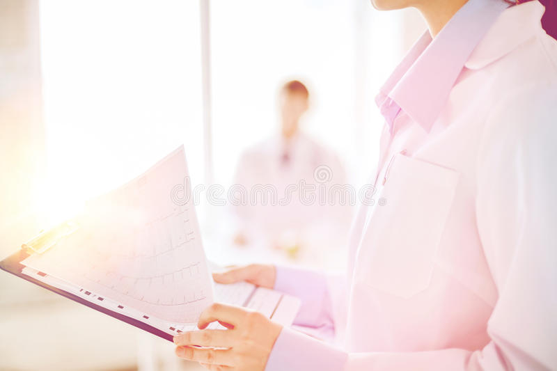 Female holding clipboard with cardiogram stock photography