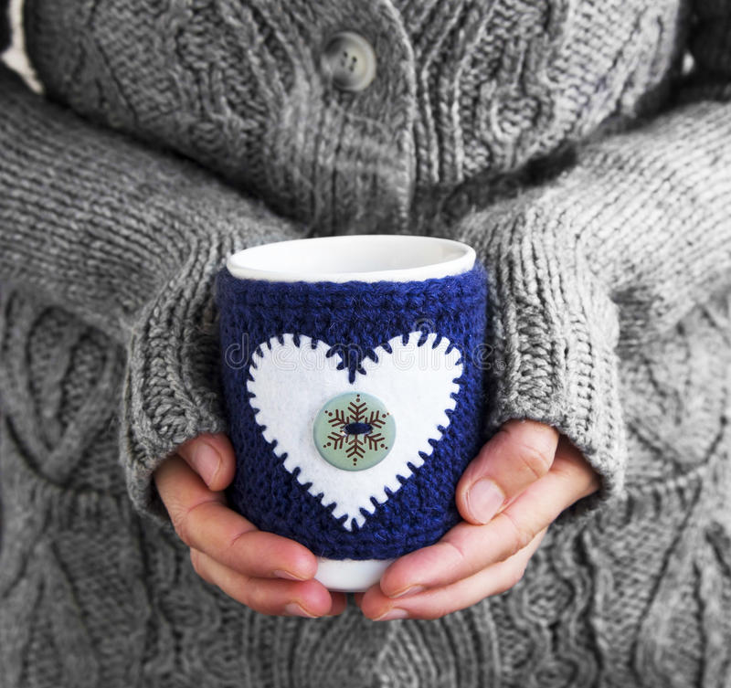 Female Holding Coffee Mug with Wool Knitted Cloth with Heart Shape. Female Holding Coffee Mug with Knitted Mug Cloth and Heart Shape in the Winter Time stock photography