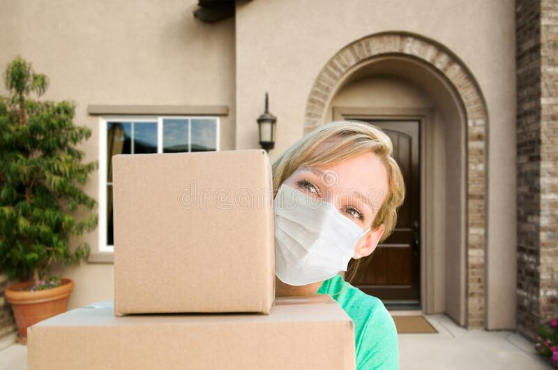 Female Holding Delivery or Moving Boxes At Front Door of House Wearing Medical Face Mask royalty free stock photography