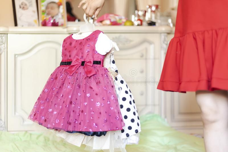 Female holding her daughter`s new dresses. Young mother getting prepared her little baby girl`s birthday dresses royalty free stock photo
