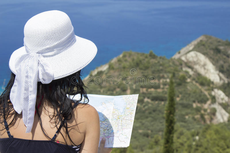 Female holding a map on the top of the hill (above the sea) royalty free stock photography