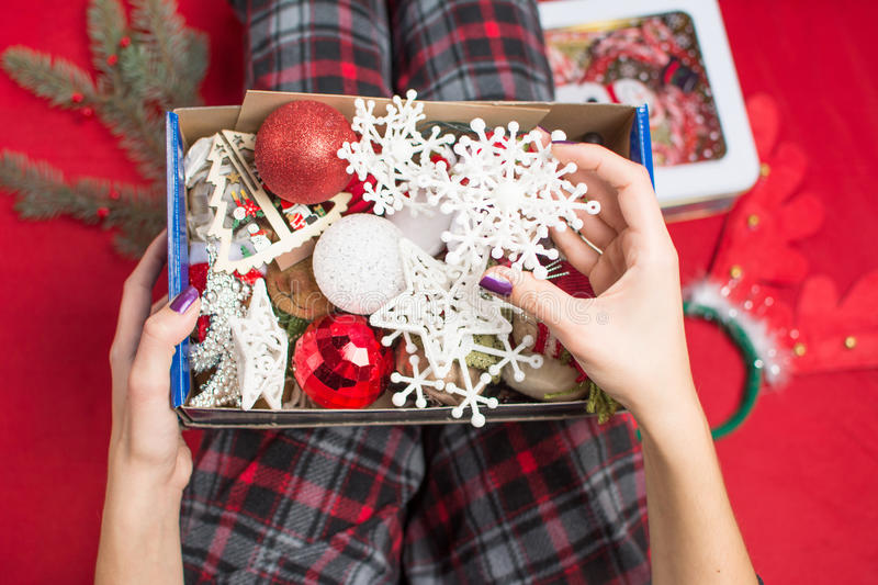Female holding an opened christmas decoration box. In pyjamas stock images