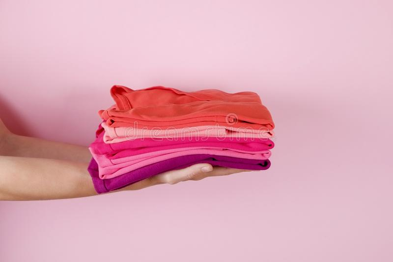 Female holding a pile of folded clothes, unisex for both man & woman, different color & material. Trip preparation concept. Close up of young woman hands stock image