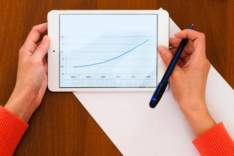 Female holding tablet with positive chart stock photography
