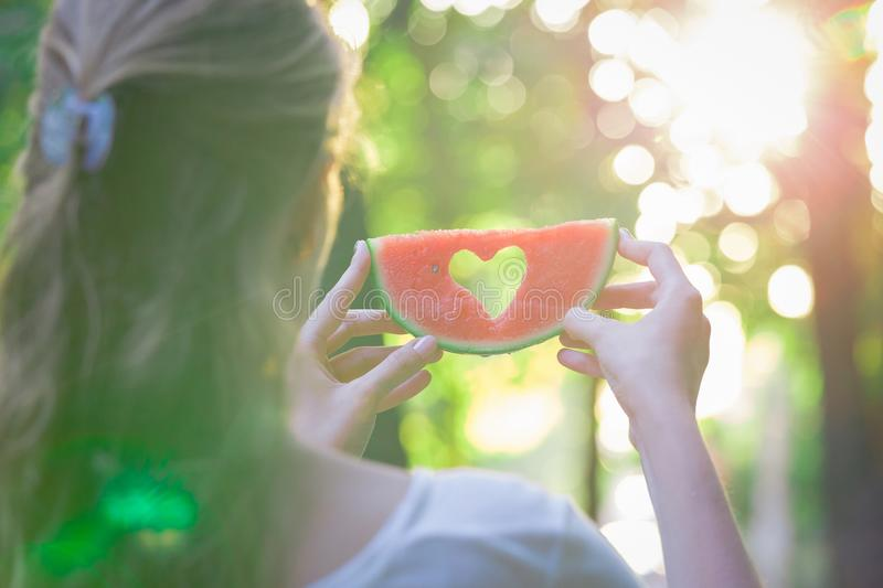 Female holding watermelon with hearth shape outdoors stock photo