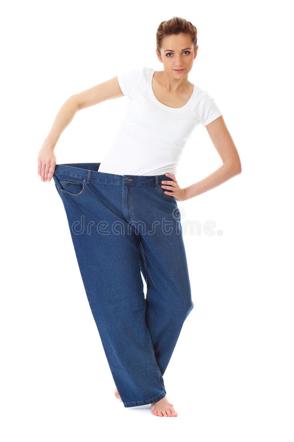 Female holds her old huge jeans, diet concept. Attractive and young female shows her old huge pair of jeans, weight loss concept, studio shoot royalty free stock photos
