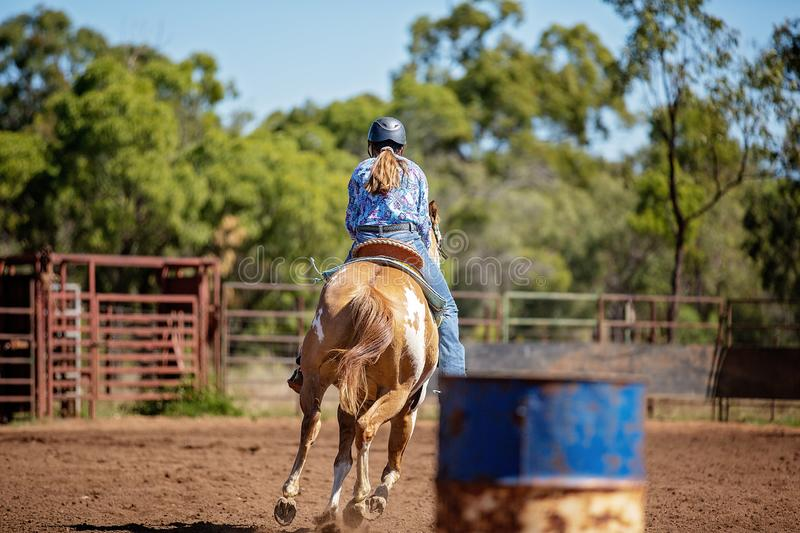 Cowgirl Competing In Barrel Racing At Outback Country Rodeo. Female horseback rider competing in barrel racing at outback country rodeo royalty free stock photography