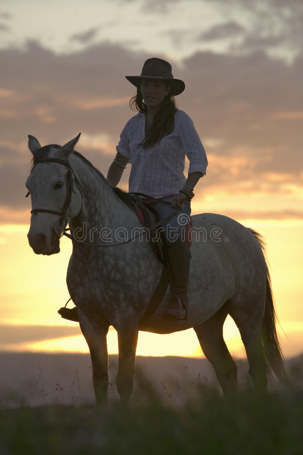Female horseback rider and horse ride to overlook at Lewa Wildlife Conservancy in North Kenya, Africa at sunset stock photography