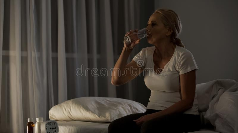 Female hospital patient drinking pills with water night, sitting bed, insomnia. Stock photo royalty free stock image
