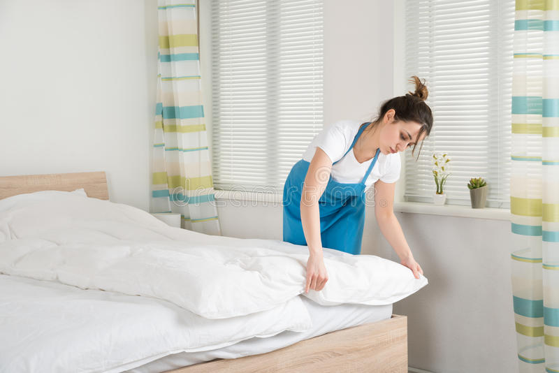 Female Housekeeper Arranging Bedsheet On Bed. Young Female Housekeeper Arranging Bedsheet On Bed In Room stock photos