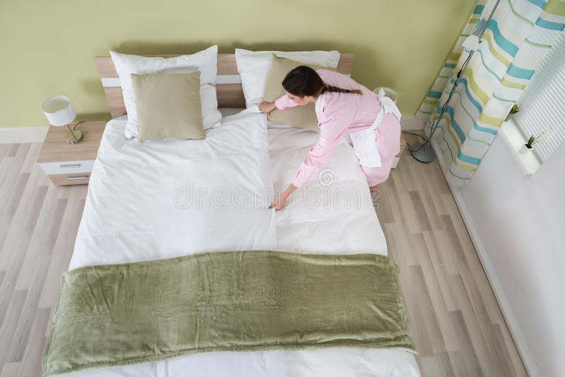 Female Housekeeper Arranging Bedsheet On Bed. Young Female Housekeeper Arranging Bedsheet On Bed In Room royalty free stock image