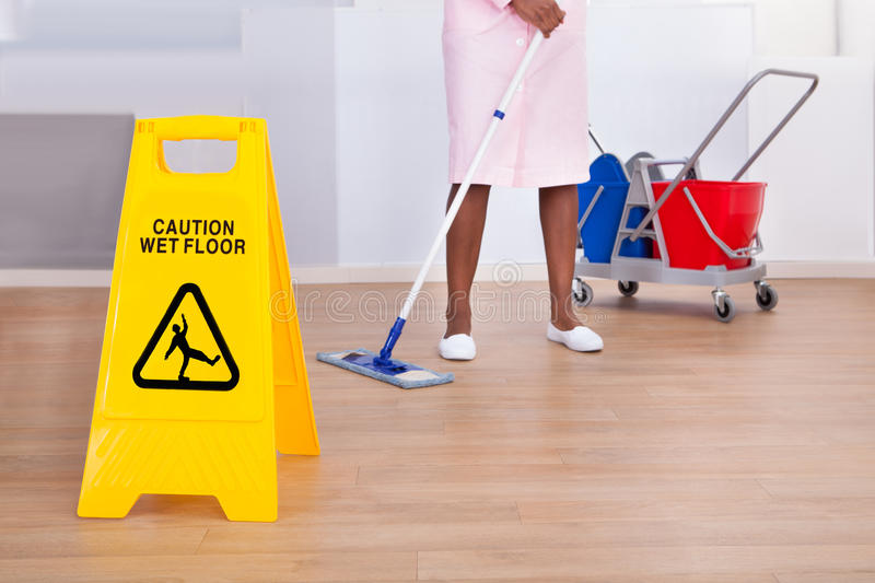 Female housekeeper cleaning floor in hotel. African American female housekeeper cleaning floor in hotel royalty free stock photo