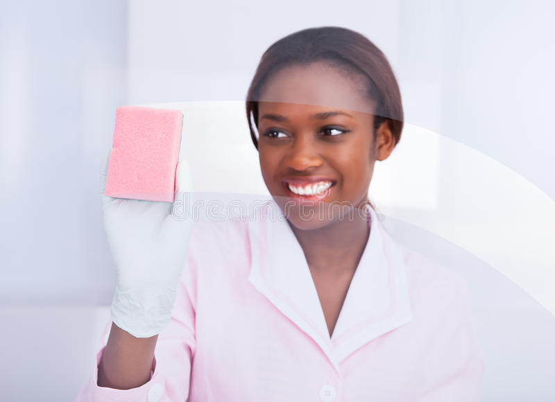 Female housekeeper cleaning glass in hotel. Happy African American female housekeeper cleaning glass in hotel royalty free stock photos