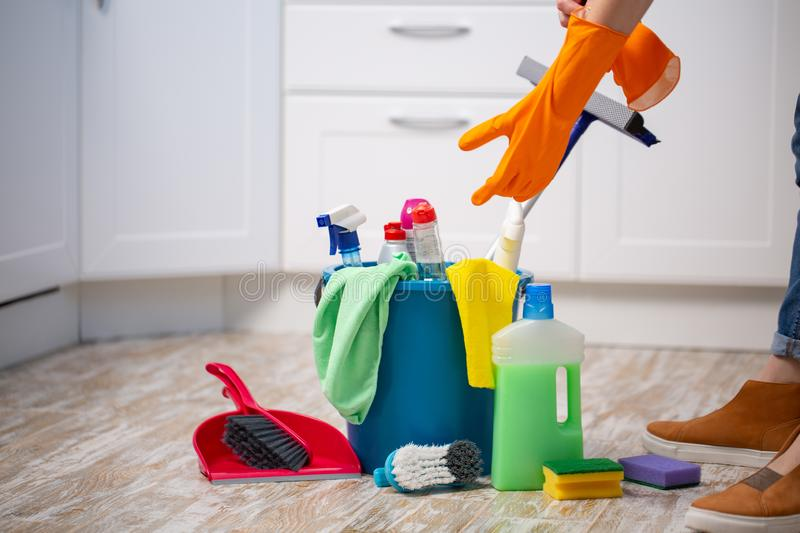 Female housekeeper while cleaning office. Woman wearing protective gloves near bucket full of cleaning supplies royalty free stock images