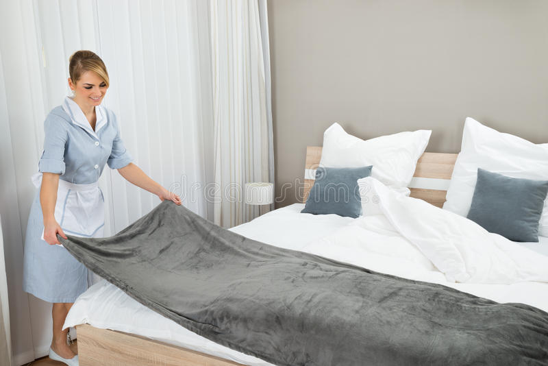Female housekeeping worker making bed royalty free stock photo